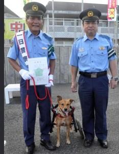 一日署長を務めた島田さん(左)と車いす犬「ラッキー」=20日、徳之島町亀津