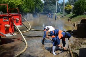 志戸桶地区の町道冠水場所での側溝の土砂撤去と路上の排水作業=6日、喜界町