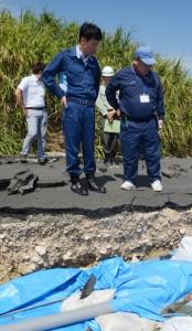 路面決壊で通行できなくなった町道など、町内3カ所を視察した三反園訓県知事(左)=18日、喜界町