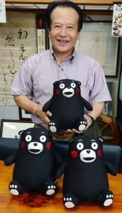 完成した大島紬の「くまモン」と原社長=22日、奄美市名瀬