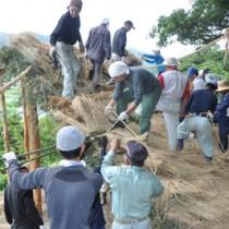 ショチョガマを組み立てる秋名・幾里の青壮年団と老人クラブの団員、ボランティアの人々=10日、龍郷町秋名