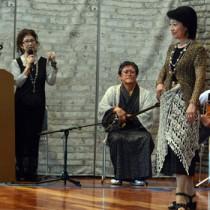 モデルが着用する作品を紹介する森さん(左)=16日、奄美パーク
