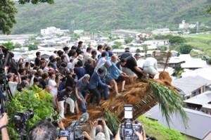 「ヨラ、メラ」の掛け声で「ショチョガマ」を揺り倒した男衆=26日午前6時30分ごろ、龍郷町