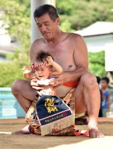 赤ちゃんの土俵入りもあった名瀬仲勝町内会の敬老会・豊年相撲=10日、奄美市名瀬仲勝町集会場