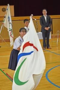 パラリンピックの旗振り体験をする児童=20日、名瀬小学校