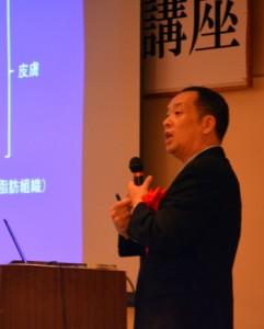 皮膚病や薬の使い方について講話する新山さん=21日、奄美市名瀬のホテル