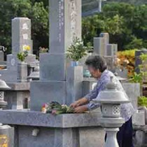 ミハチガツ行事の終わり「ドゥンガ」を継承し墓参する住民=4日、龍郷町秋名
