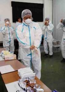 防護服の着用実演で、防疫体制の手順を確認する参加者=25日、奄美市名瀬の県大島支庁