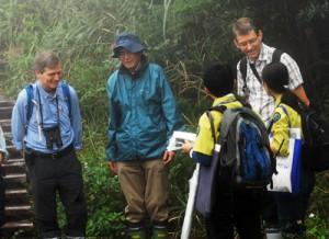 環境省の職員から説明を受けるスコット・パーキン氏(左)とバスチャン・ベルツキー氏(右奥)=13日、大和村の湯湾岳登山道入り口
