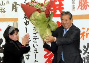 当選確実の知らせを受けて花束を受け取る金子氏=22日午後8時10分ごろ、鹿児島市東谷山