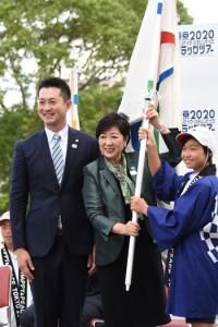 フラッグをリレーした(左から)ツアーアンバサダーの宮下純一さん、小池百合子東京都知事、地元の児童=3日午後、鹿児島県庁