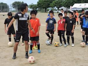 子どもたちに指導する鹿児島Uの新中さん(左)=15日、喜界町総合グラウンド