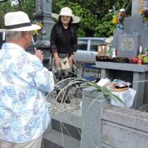 墓地にシバを飾り、先祖に手を合わせる住民=1日、喜界島小野津の共同墓地