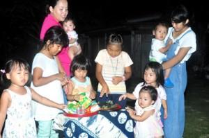 「トゥンガ、トゥンガ」と声を上げながら、供えられた餅や菓子をとる子どもたち=4日、与論町
