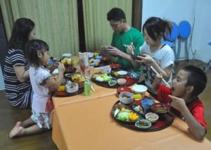 オープンした子ども食堂の料理を食べる親子連れ=14日、徳之島町亀津