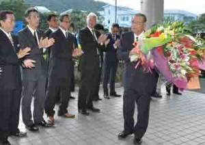 花束を手に初登庁する竹田泰典新町長=10日、龍郷町役場