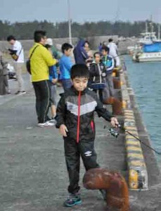 イカ釣りに挑戦する参加者=18日、奄美市笠利町の宇宿漁港