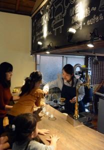 いれたてのコーヒーを振る舞う重田さん(右)=12日、宇検村湯湾