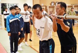 池畑さん(右)のアドバイスを受けながらスクワットトレーニングを体験する生徒=11日、名瀬中学校