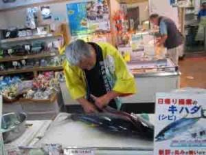 キハダマグロの解体ショーを披露する瀬戸内漁業集落の久野弘仁さん=5日、鹿児島市