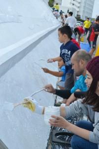 ミコノス通りの白壁のモニュメントを、きれいに塗り直す参加者=5日、与論町