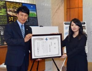 三反園知事から表彰状を受け取る勝野さん(右)=13日、鹿児島市の県庁