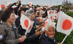 空港駐車場の一角で、小旗を振って両陛下の来島を歓迎する島民ら=16日午後4時35分ごろ、和泊町国頭