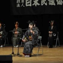 練習の成果を発揮し、得意の曲を歌う出場者=26日、龍郷町