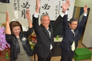 早々と当確を決め、万歳三唱で喜ぶ朝山毅氏(中央)=19日午後8時45分ごろ、奄美市名瀬の選挙事務所