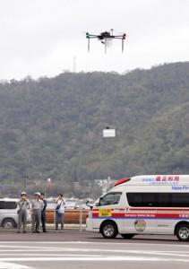 離島と想定した佐大熊ヘリポートで降下し、医療資機材を降ろす小型無人機=13日、奄美市名瀬
