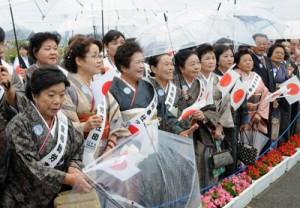雨の中、紬姿で天皇、皇后両陛下の到着を待つパナウルゆいまぁる会のメンバー=17日午前11時10分ごろ、与論空港