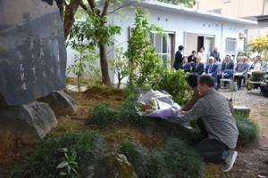 文学碑に献花する(手前から)島尾伸三さんと潤井理事長=12日、奄美市名瀬