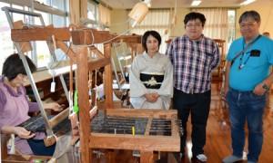 清田さんが織り上げた大島紬を着て家族とともに奄美大島を訪れた阿部綾子さん=2日、龍郷町大島紬技能養成所