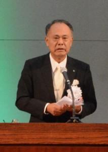「式典は新たなスタート」と式辞を述べた元田村長(下)。オープニングを飾った芦検集落伝統の稲すり踊り=5日、宇検村総合体育館