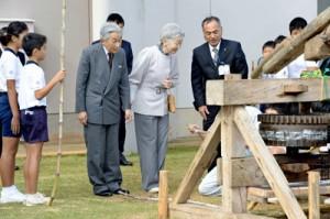 黒糖づくりに使うサタグルマをご覧になる天皇、皇后両陛下=18日午前11時21分、和泊町国頭の国頭小学校(代表撮影)