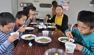 町内各飲食店の創作どんぶり料理を味わう人たち=23日、和泊町