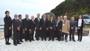 慰霊碑を前に立つ沖縄、宇検村の関係者