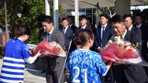 花束を受取る(右から)福原峰夫野手総合コーチ、佐野恵太選手=2日、奄美空港