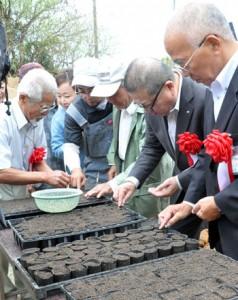 種の植え付けを行う吉玉会長ら(写真左)=13日、伊仙町伊仙
