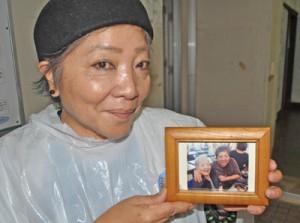 母・山川シズさんとの親子スナップ写真を手に、笑顔を見せる上田さん=17日、知名町