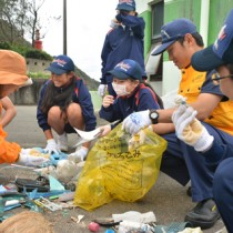 奄美海保の職員と漂着調査で集めたごみを分類する龍北中の生徒ら=2016年4月28日、龍郷町の嘉渡海岸