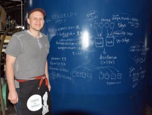 焼酎造りのメモが書かれたタンクを前にチャールズさん=21日、奄美市名瀬の西平酒造