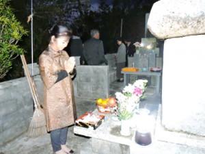 墓前に手を合わせて先祖に感謝する女性=1日、喜界町荒木
