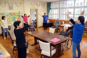 旧坂嶺小の校舎を改装した小規模多機能ホーム「十五夜」で、体操を楽しみながら交流する高齢者ら