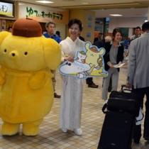 成田からの到着客を出迎える山室副社長(中央)とポムポムプリン=16日、奄美市笠利町の奄美空港