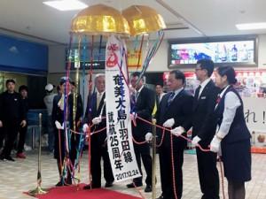 くす玉を割って羽田―奄美大島線の就航25周年を祝う関係者=24日、奄美市笠利町の奄美空港