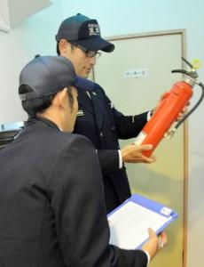 消火器の有効期限を確認する消防職員=22日、奄美市名瀬