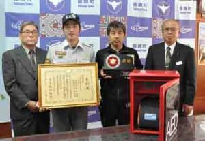 消防防災科学技術賞で優秀賞を受賞した野村さん(右から2人目)と龍郷町幹部ら。手前は屋外用AED収納ボックス=15日、龍郷町役場