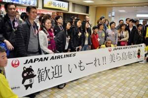 歓迎セレモニーで記念撮影するシンガポールからのツアー客ら=24日、奄美空港