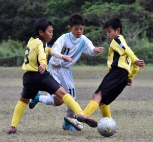【A級決勝・TFA―亀津SSS】ゴール前でボールを奪い合う両チームの選手=17日、古見方多目的広場